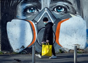 Milan, Italy A man walks with his groceries beside a mural that portrays a person wearing a gas mask