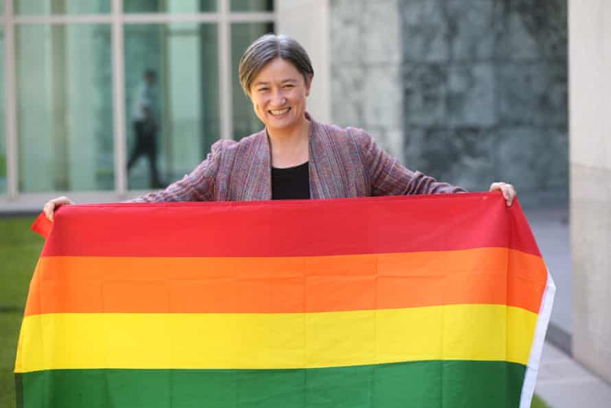 Penny Wong carries the rainbow flag in celebration.