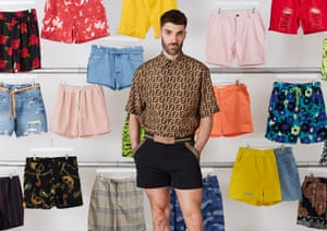 Joe Stone, wearing short shorts, in front of lots of pairs of shorts hanging up