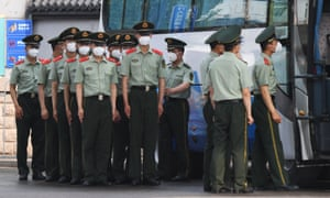 Chinese paramilitary police prepare to guard entrances to the closed Xinfadi market in Beijing on 13 June 2020.
