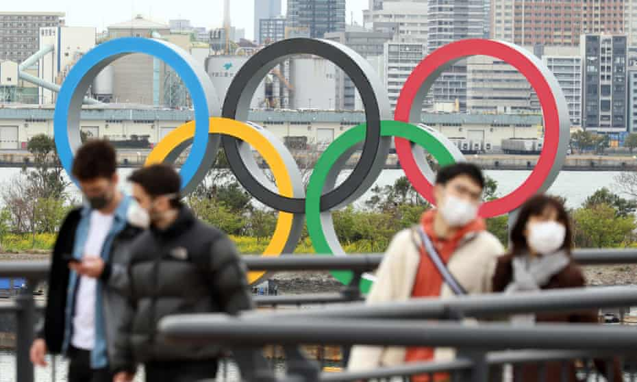 Pedestrians wearing face masks walk past the Olympic rings in Tokyo.