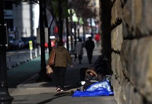 People walk past Robin Riddick as she makes a makeshift space for sleeping along First Street, NE near Union Station in Washington, D.C.