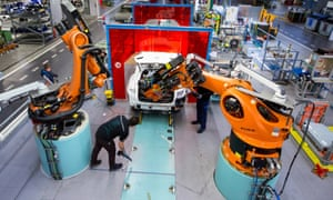 Employees work alongside robotic arms, in a Mercedes-Benz factory in Bremen, Germany
