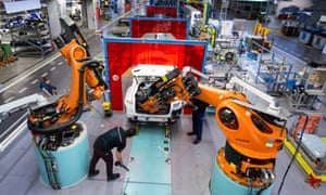 In Bremen, Germany, a hybrid car is assembled by employees working with robotic arms.