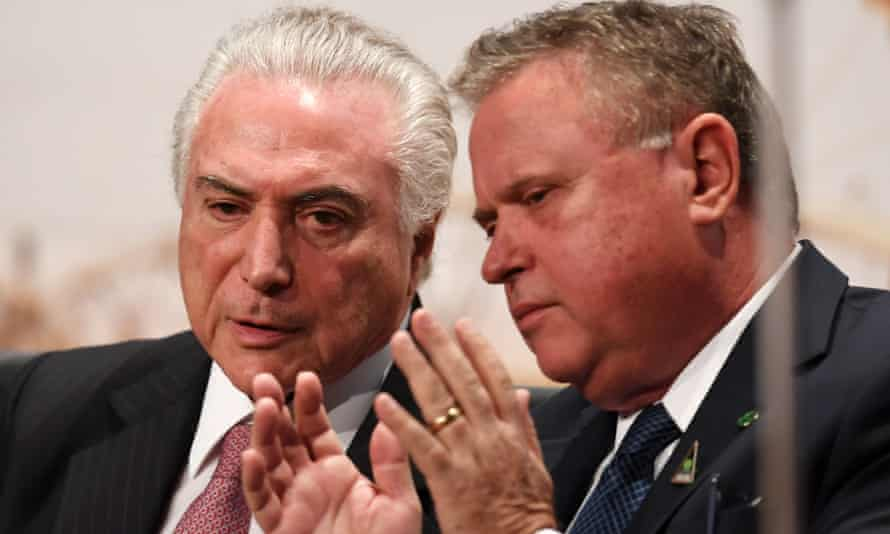 The Brazilian president, Michel Temer, speaks with the agriculture minister, Blairo Maggi, whose farm was targeted in the invasion.