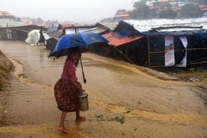 A young girl makes her way home after collecting relief aid during a rain storm at Balukhali refugee camp