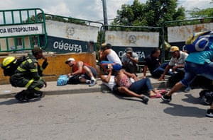 People take cover behind barriers as shots are fired near the Simon Bolivar bridge on the border between Colombia and Venezuela.