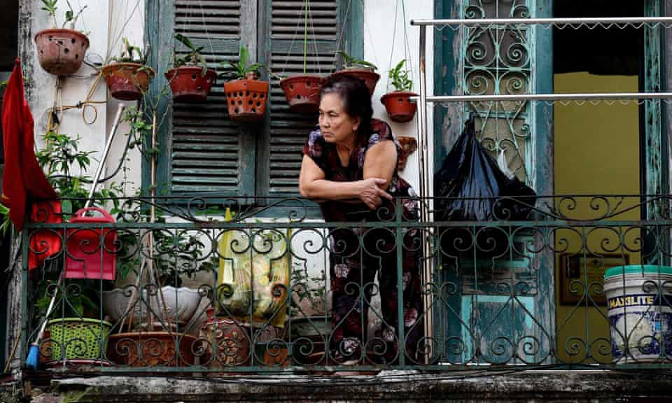 A resident looks out from the balcony of her home in Hanoi.
