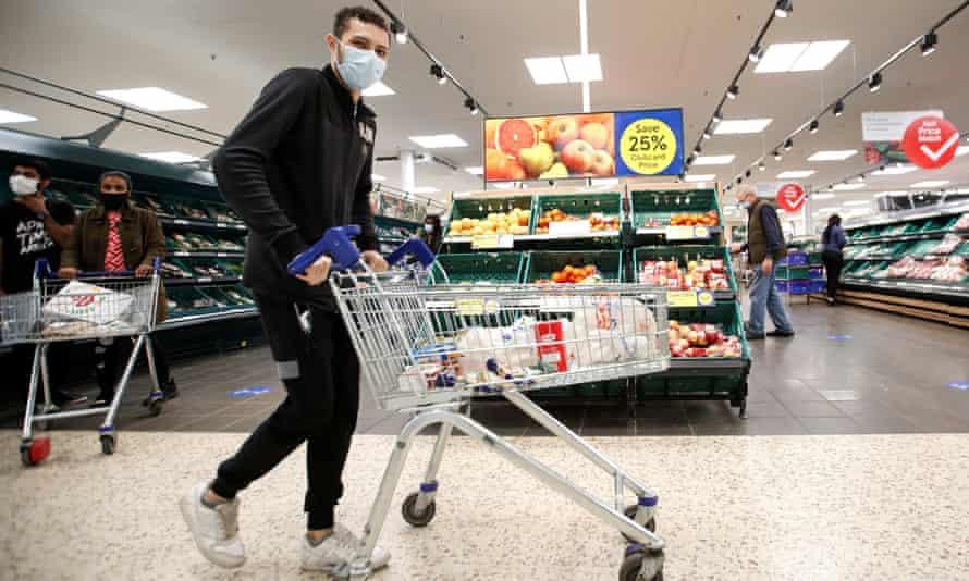 A man wearing a face mask pushes a shopping cart at a Tesco supermarket