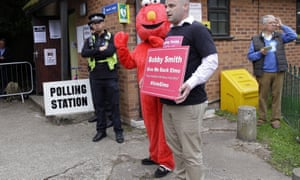 Bobby Smith and a person wearing a costume of the Muppet character Elmo outside the polling station.