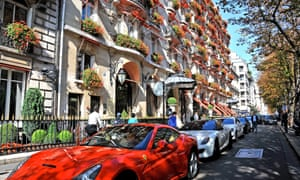 Ferraris and other luxury cars parked outside Hotel Plaza Athénée in Paris, France