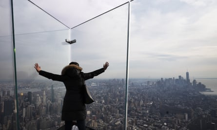 A visitor looks through the thick glass plates that line a triangular-shaped outdoor observation deck called The Edge at Hudson Yards in New York.