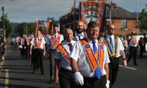 Orange Order members march past Ardoyne shops on the Crumlin Road in Belfast as part of the 12 July celebrations.