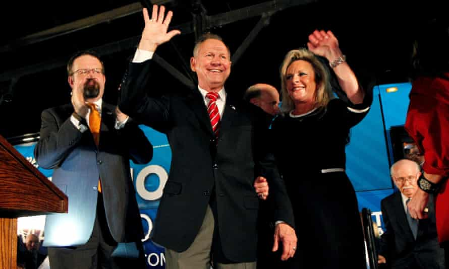 Ex-Trump adviser Sebastian Gorka applauds as Roy Moore and his wife Kayla wave in Montgomery this week.