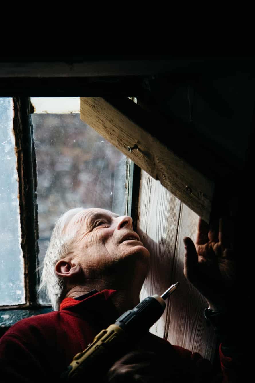 A bothy volunteer drilling a window in order to repair it.