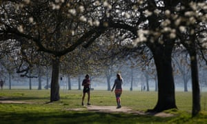 People are seen exercising in a park in South London