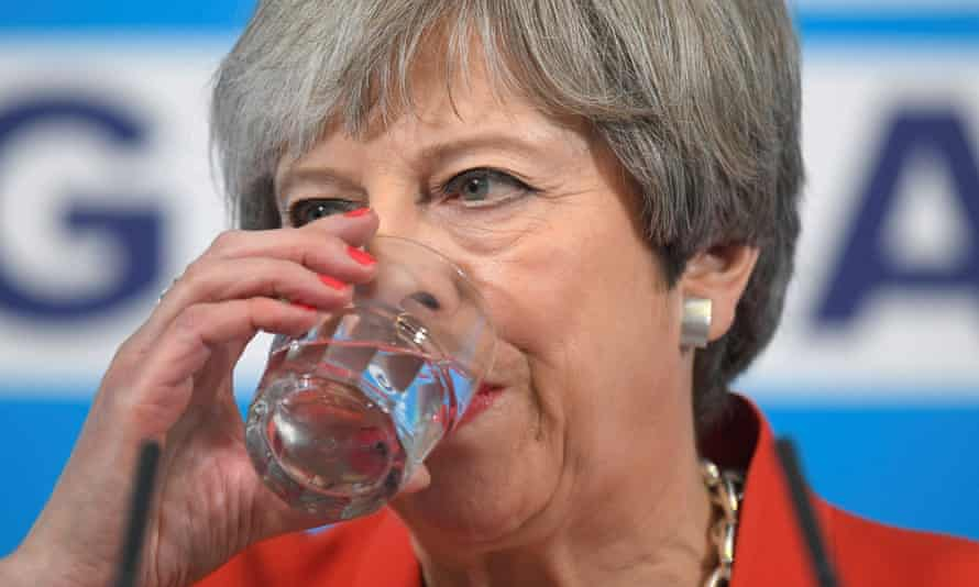 Theresa May holds a glass to her lips