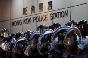 Hong Kong Police officers stand guard outside Mong Kok police station during the demonstration against the extradition bill