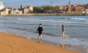 Two women enjoy San Lorenzo beach in Gijon, Asturias, northern Spain