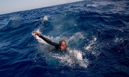 A migrant tries to board a boat belonging to the German NGO Sea-Watch in the Mediterranean, 2017