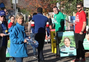 How-to-vote cards are handed out at a voting booth in Balwyn for the seat of Kooyong.