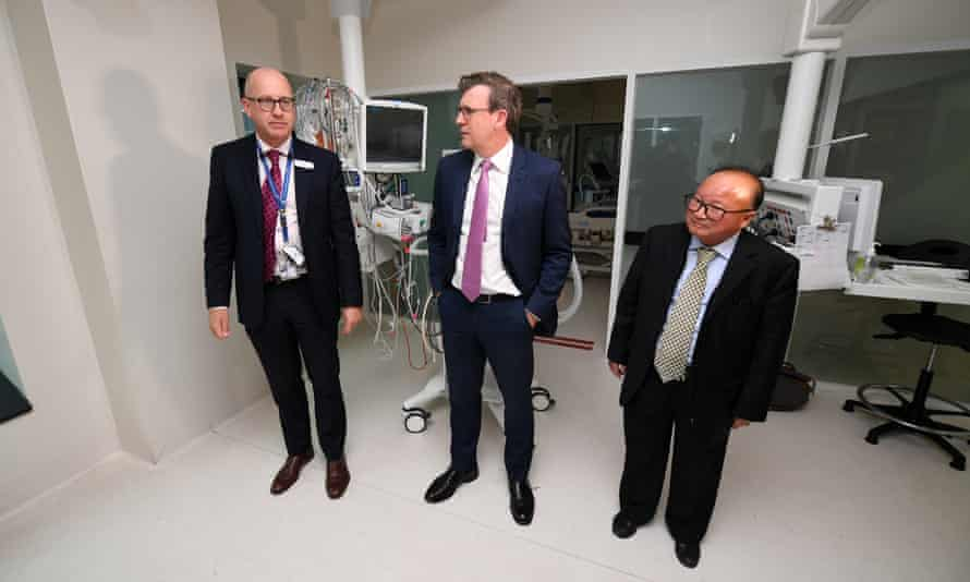 Acting Minister for Immigration, Alan Tudge (centre) and Oceania Federation of Chinese Organisations president Sunny Duong (right) tour the intensive care unit at the Royal Melbourne hospital, after Duong donated more than $37,000 to the hospital.
