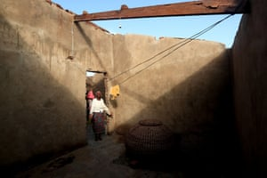 Tchacaca Quembo inside her roofless house, damaged in Cyclone Idai.