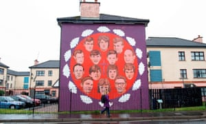 A pedestrian walks past a mural commemorating the victims of the 1972 Bloody Sunday killings in the Bogside area of Derry.