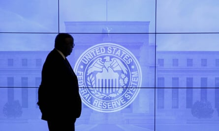 A guard walks in front of the Federal Reserve image in Washington DC