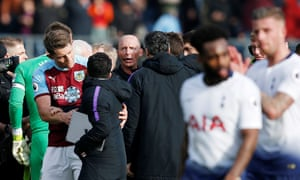 Mike Dean is surrounded by Tottenham's coaching staff after the final whistle.