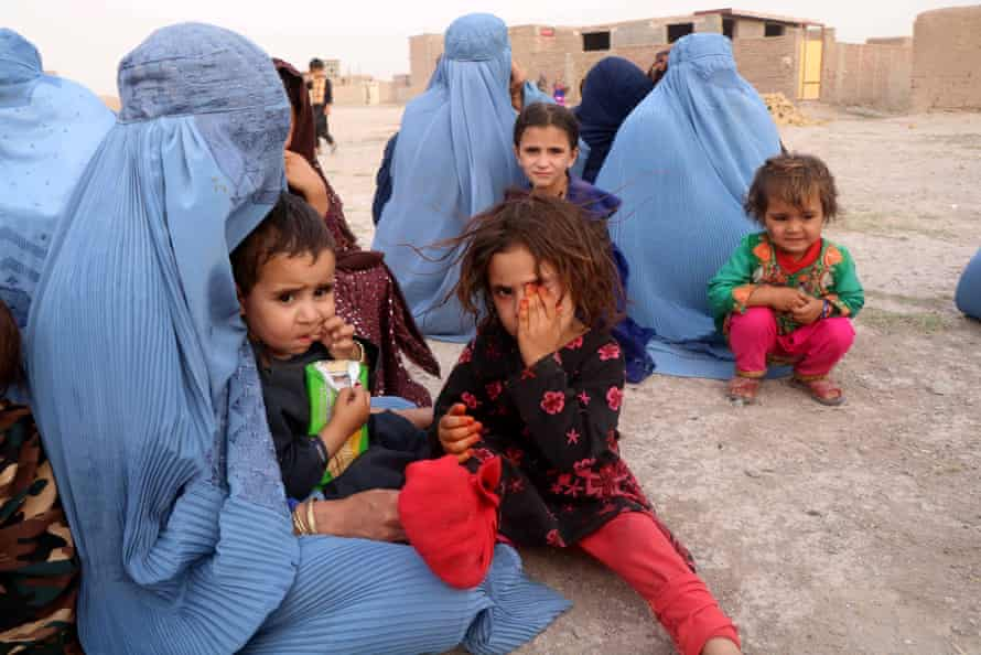 People displaced from restive Ghor district wait for government assistance at a temporary shelter in Qaderabad village in neighbouring Herat province