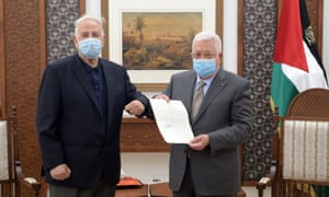 Palestinian president Mahmoud Abbas (R) signs the decree for holding parliamentary and presidential elections on May 22 and July 31, respectively, after meeting with chairman of the Palestinian central elections commission Hanna Nasser (L) in Ramallah, West Bank