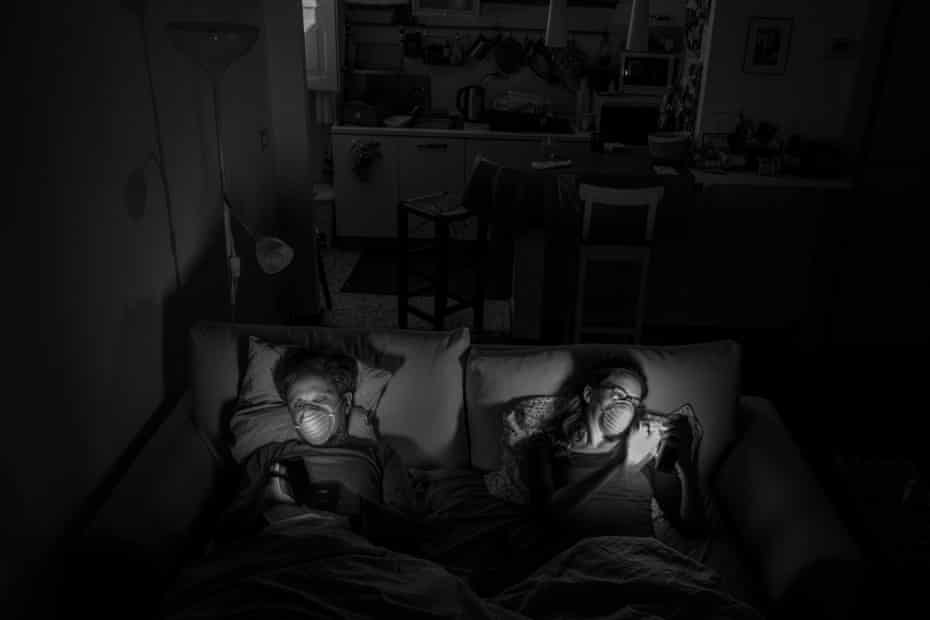 On the sofa bed before watching a movie. Most of the time when they are together Alessio and Marta have to wear masks. At night they sleep in separate beds.