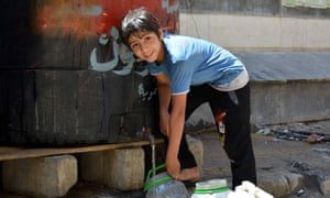 A child fills a container with water in Yarmouk last month.