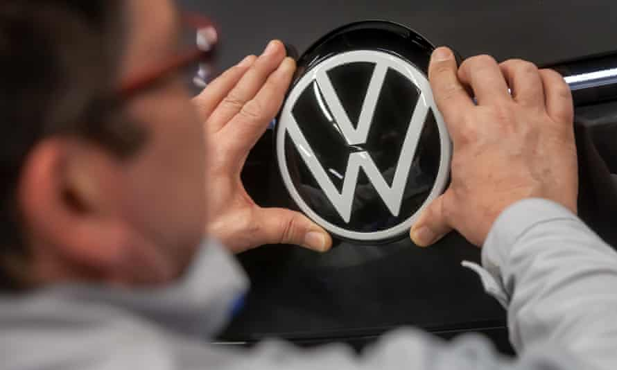 A worker attaches a Volkswagen logo to a car.
