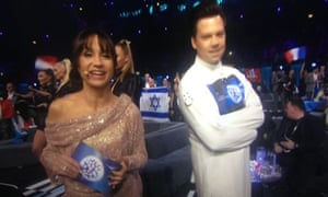 Petra Mede with a man wearing a Eurovision-branded straitjacket.