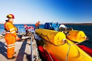 Workers preparing to tow a wave energy generator in the Orkney Isles.