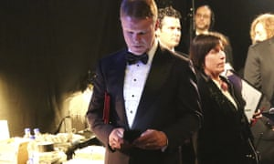 PwC accountant Brian Cullinan holds winners envelopes under his arm while using his cellphone backstage at the Oscars. The Academy president blamed Cullinan's distraction for the error.