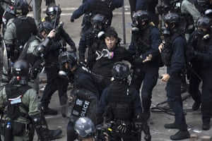 Riot police surround a protester as he tries to flee the university