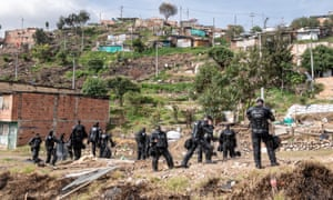A group of riot police is waiting orders to position themselves inside the slum of Altos de la Estancia on 11 May. During the past days, several evictions were processed, and the houses destroyed.