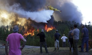 People watch a firefighting plane drop water to stop a raging forest blaze reaching their houses near Mação, central Portugal.