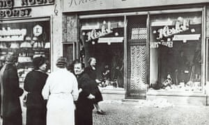 In November 1938 a group of people stand outside a Jewish-owned shop in an unnamed German town after the Kristallnacht, a night of Nazi-incited mass riots against Jewish people and property.