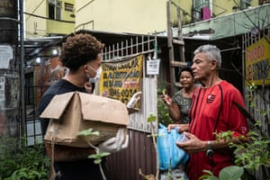 Residents of the City of God favela distribute food parcels