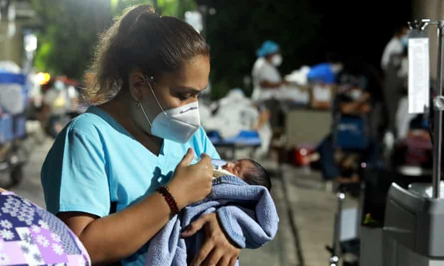 A nurse takes care of a baby outside a hospital after patients and personnel were evacuated after an earthquake in Acapulco, Mexico.
