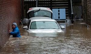 A boy wades through a flooded alleyway in Pontypridd.