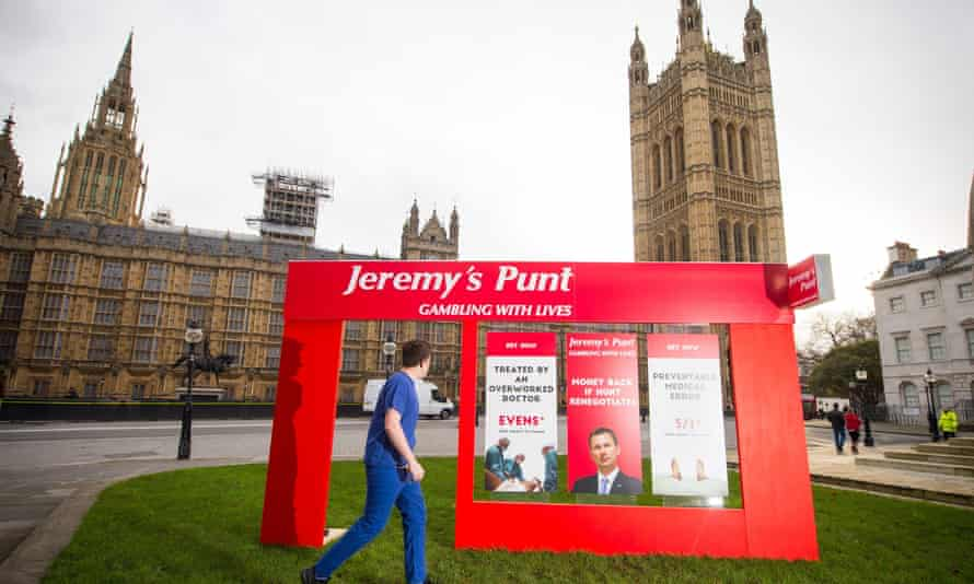 A campaigner dressed as a junior doctor walks past a fake betting shop storefront outside the Houses of Parliament.