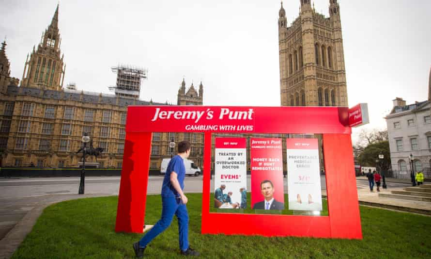 A campaigner dressed as a junior doctor is seen with a fake betting shop storefront outside the Houses of Parliament in Westminster.