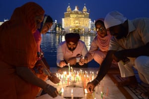 Sikh devotees light candles at the Golden Temple in Amritsar, India