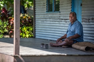Josateki sits in front of a house in Raviravi, Fiji