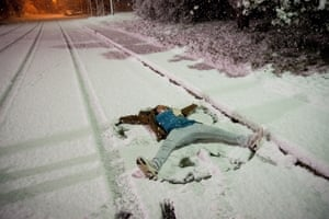 A young person makes a 'snow angel' on the ground.